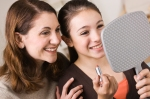 mother-teaching-tween-daughter-to-apply-lipstick